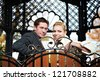 Happy bride and groom on decorative bench at wedding walk - stock photo