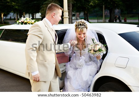Happy bride and groom out of wedding limousine - stock photo