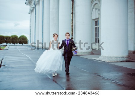 happy bride and groom walking among the columns  - stock photo