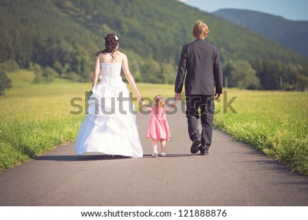 happy bride and groom with their daughter walking on the road - stock photo