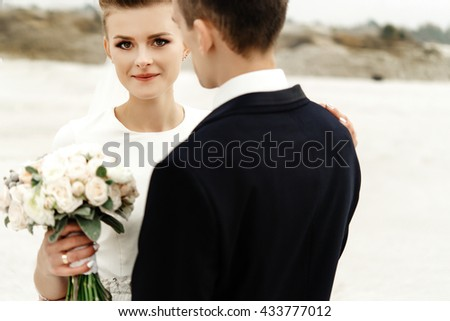 happy bride and stylish groom at sandy coast hugging and smiling, luxury wedding