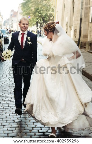 happy bride and stylish groom running with funny emotions on the background old sunny city