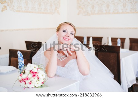 Happy bride at the reception table. young bride in restaurant sit by banquet table - stock photo