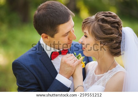 happy bride, groom holding hands in green park, kissing, smiling, laughing. lovers in wedding day. happy young couple in love. new family lifestyles. beautiful people. nature background. woman man - stock photo