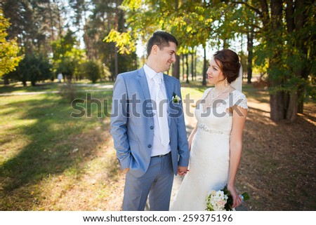 happy bride, groom standing in green park, kissing, smiling, laughing, embracing. lovers in wedding day. happy young couple in love. beautiful healthy people. nature green background. woman man - stock photo