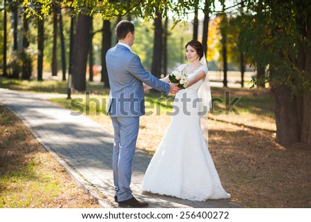 happy bride, groom standing in green park, kissing, smiling, laughing. lovers in wedding day. happy young couple dancing. new family lifestyles. beautiful healthy people. nature background. woman man - stock photo