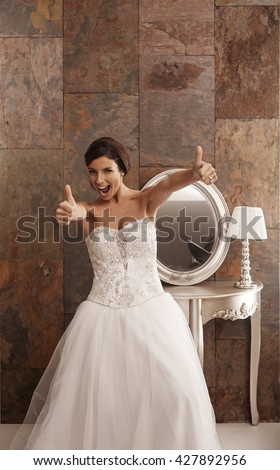 Happy bride in wedding dress showing thumbs up. - stock photo