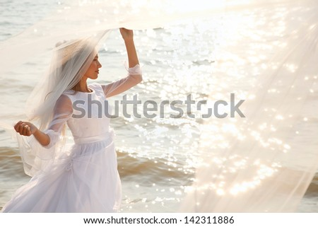 Near sparkling water and holding her flying veil stock photo