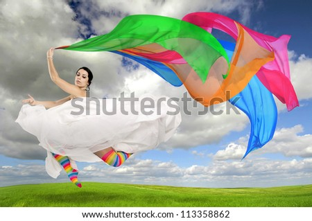Happy bride jumping with colorful stockings and scarfs outdoors