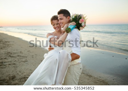 Happy bride leans to groom's face while he hold her in his arms on the sea