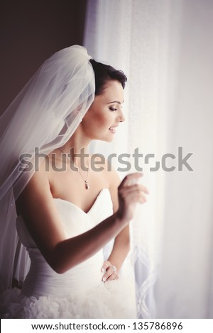 Happy Bride looking in window - stock photo