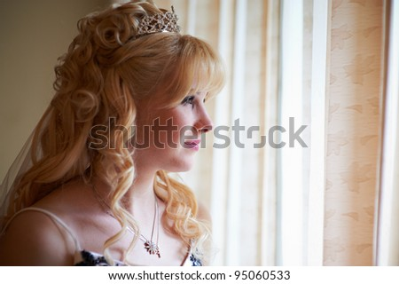 Happy bride looking out the window in wedding day - stock photo