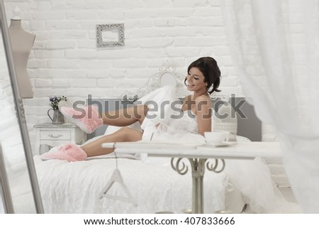 Happy bride lying on bed in wedding dress and pink slippers. - stock photo