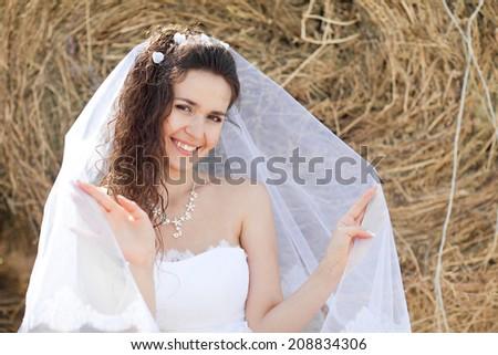 happy bride near the hay - stock photo