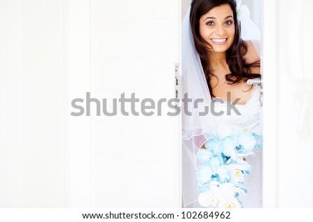 happy bride opening doors at doorway - stock photo