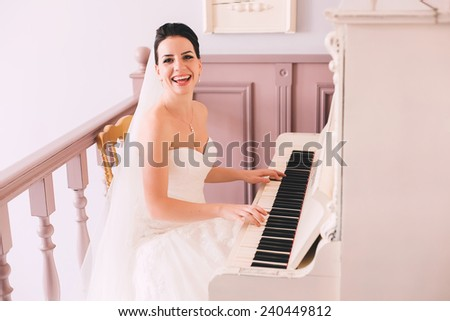 happy bride playing the piano indoors - stock photo