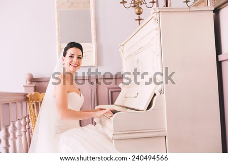 happy bride playing the white piano indoors - stock photo