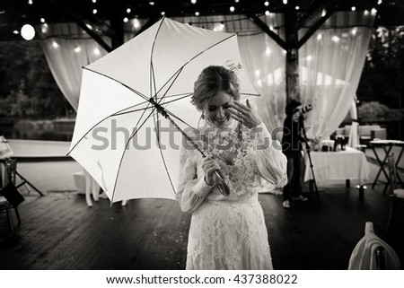 Happy bride walks into the restaurant pavilion holding an umbrella over her - stock photo