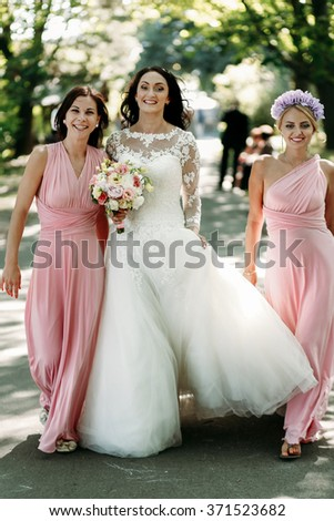 Happy bride with bridesmaids at  wedding walk outdoors - stock photo