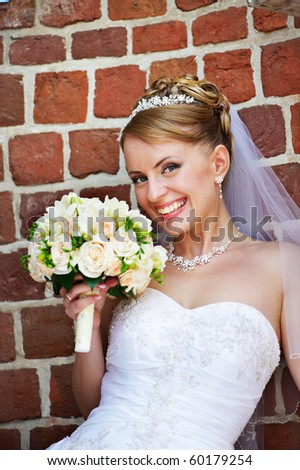 Happy bride with wedding bouquet on wedding walk - stock photo