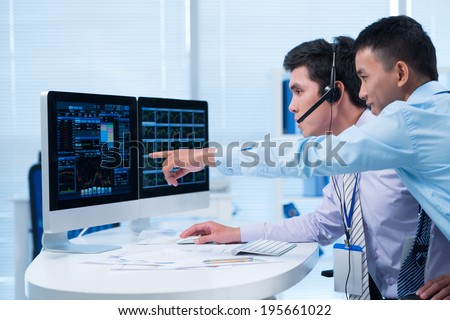 Happy broker showing some ascending to his colleague - stock photo
