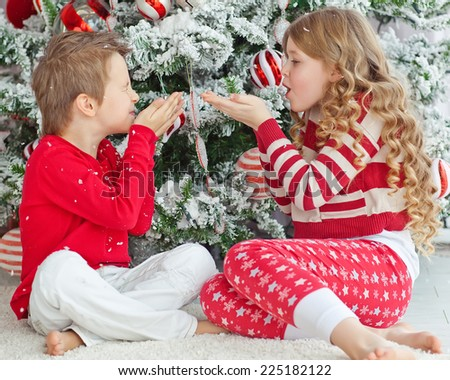 Happy brother and sister are embracing near Christmas tree. little friends enjoying New Year party, Christmastime holidays, best friends, happiness concept - stock photo