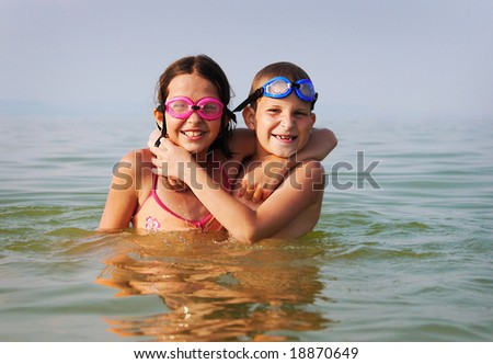 Happy brother and sister embrace each other in the water