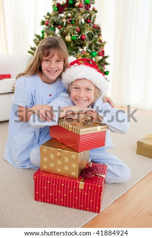Happy brother and sister holding Christmas presents and smiling at the camera