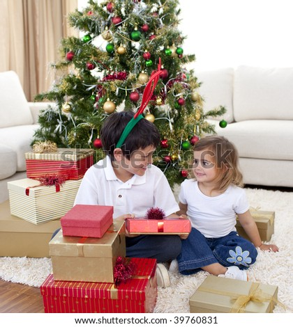 Happy brother and sister looking at Christmas gifts at home