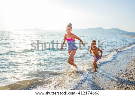 Happy brother and sister running at tropical beach against sunlight - stock photo