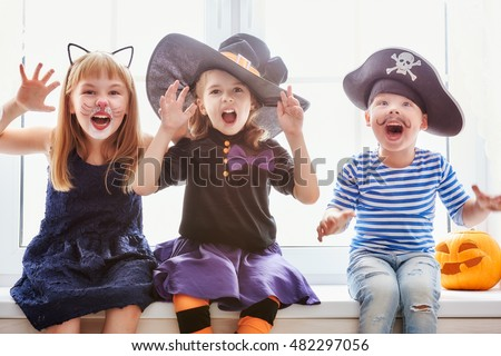 Happy brother and two sisters on Halloween. Funny kids in carnival costumes indoors. Cheerful children play sitting on the window.