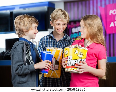 Happy brothers and sister conversing while holding snacks against cinema concession stand - stock photo