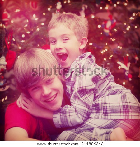 Happy Brothers in front of a christmas tree. Instagram effect - stock photo