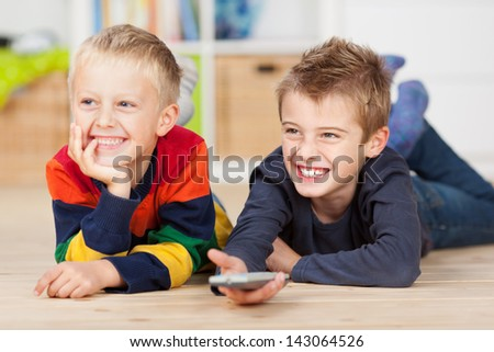 Happy brothers with remote control watching television while lying on hardwood floor - stock photo