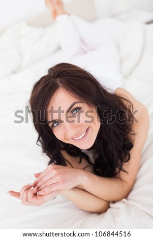 Happy brown-haired woman lying on her blanket in her bedroom