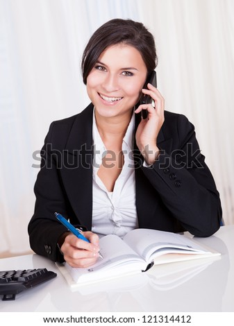 Happy brunette business woman takes notes whilst listening to someone on her mobile phone - stock photo