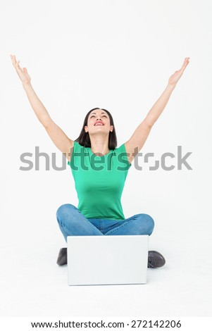 Happy brunette cheering in front of her laptop on white background - stock photo