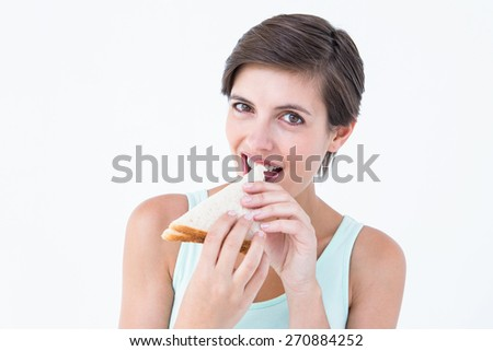 Happy brunette eating sandwich on white background - stock photo