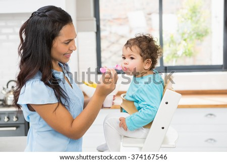 Happy brunette feeding her baby in the kitchen - stock photo