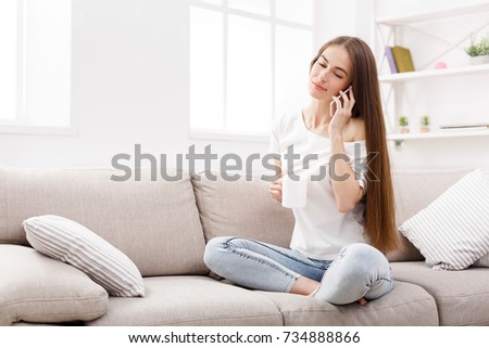 Happy brunette girl at home talking on mobile and drinks coffee on beige couch in light livingroom