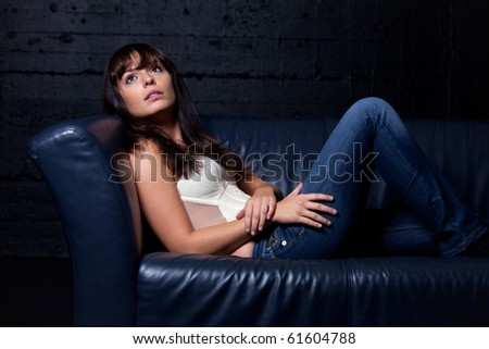 happy brunette girl in a white top on a couch