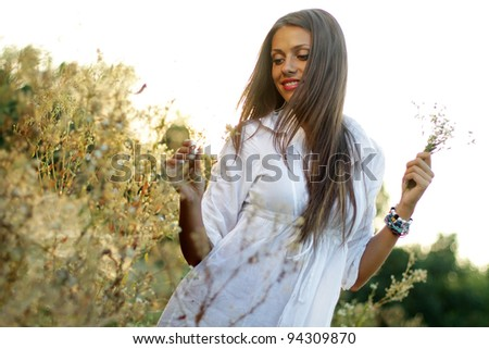 Happy brunette girl relaxing in the field at sunset - stock photo