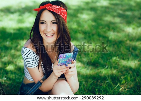 Happy brunette girl, sitting on the grass with mobile phone. Wearing red bandana and striped top. Sunny day. Copy space. - stock photo