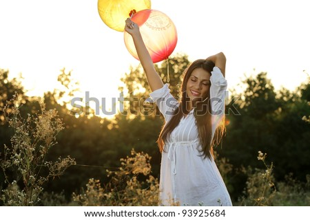 Happy brunette girl with balloons relaxing in the field at sunset - stock photo
