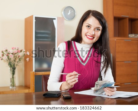 Happy brunette girl with money and documents  in home interior