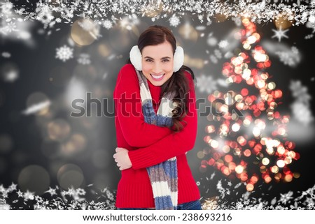Happy brunette in winter clothes smiling at camera against shimmering christmas tree of lights - stock photo