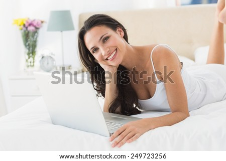 Happy brunette using her laptop at home in bedroom - stock photo
