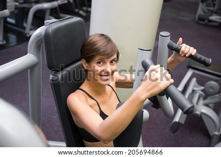 Happy brunette using weights machine for arms at the gym