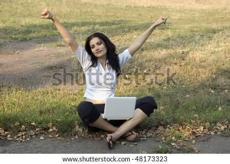 Happy brunette with laptop - stock photo