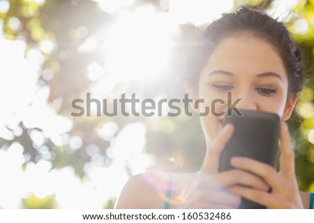 Happy brunette woman texting with her smartphone in a park - stock photo